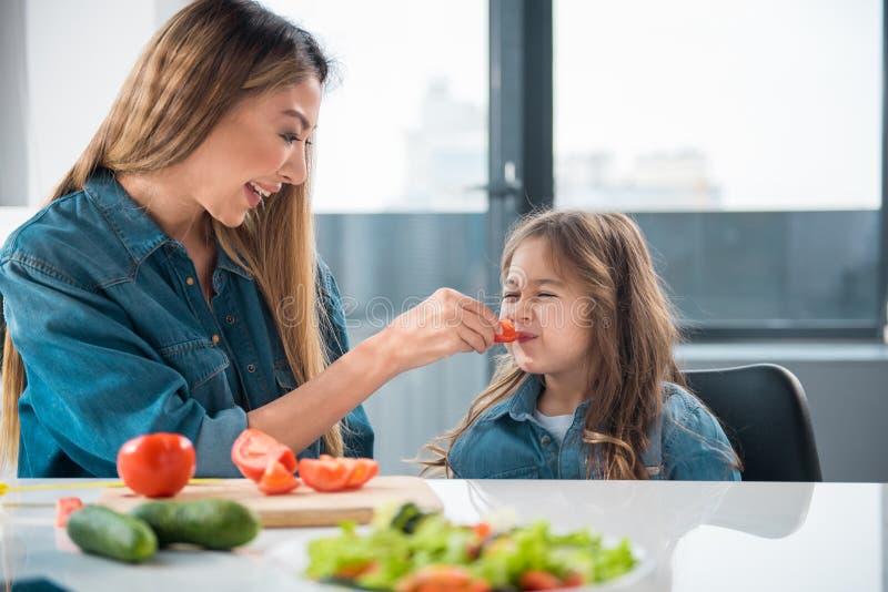 Madre asiática que alimenta a su niño por el tomate imágenes de archivo libres de regalías