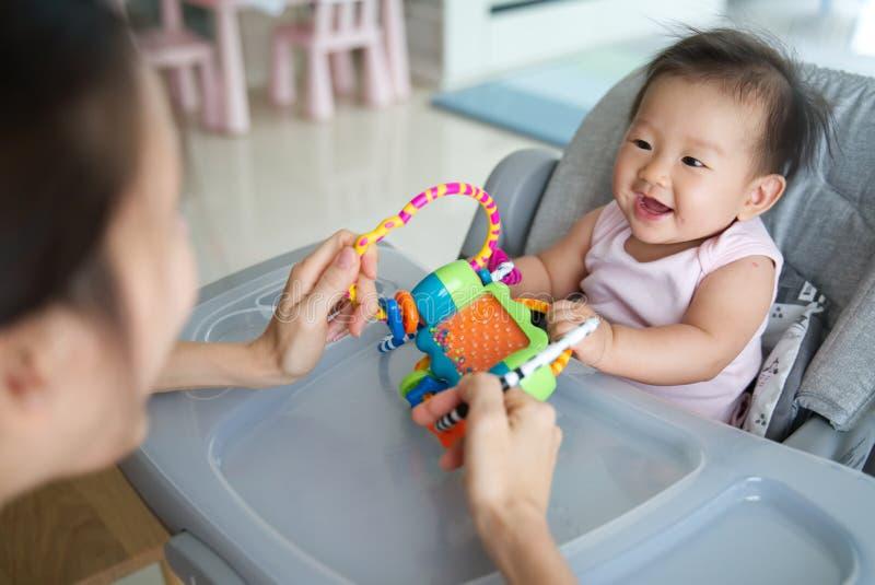 Madre asiática que juega el juguete con su bebé que se sienta en la silla dinning en casa Son gozan el jugar así como felicidad fotos de archivo