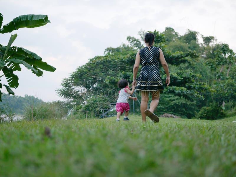 Madre asiática que mantiene la mano de su pequeña hija y tener un paseo unida en un campo de hierba verde al aire libre por la or fotos de archivo libres de regalías