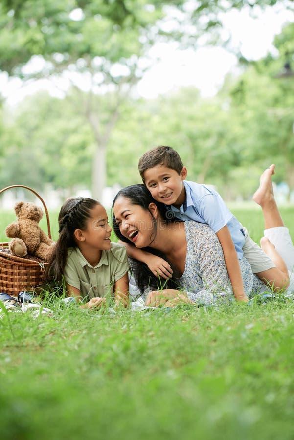 Madre asiática y niños que se divierten en comida campestre imagenes de archivo