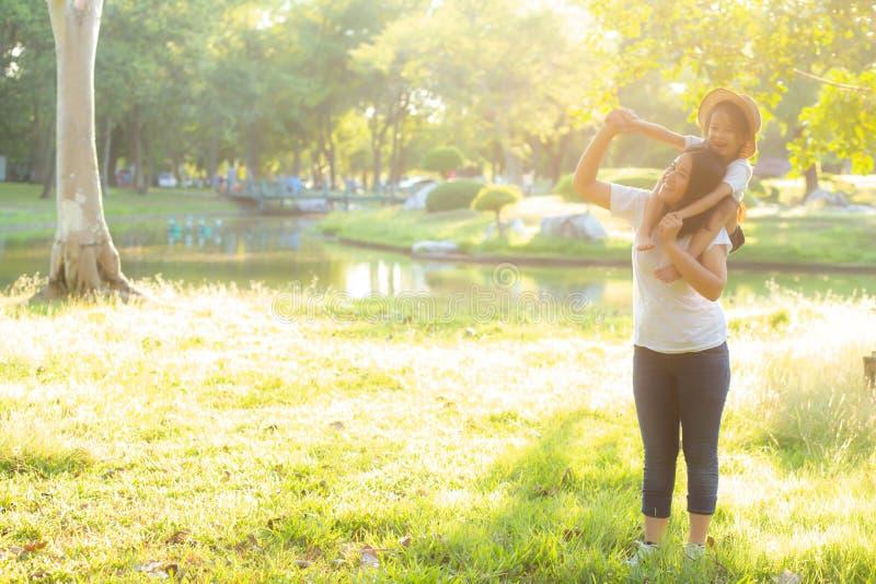 Madre asi?tica joven hermosa que lleva a poca hija con la sonrisa, paseo del ni?o el cuello en mam? con felicidad y alegre foto de archivo