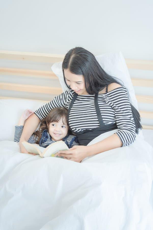 Madre asiatica che legge libro divertente con sua figlia sveglia fotografia stock libera da diritti