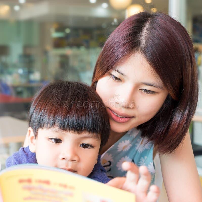 Madre asiatica che legge un libro il suo bambino fotografia stock libera da diritti