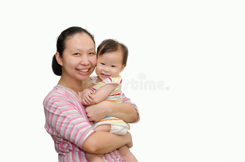 Madre asiatica che tiene la neonata adorabile del bambino immagine stock