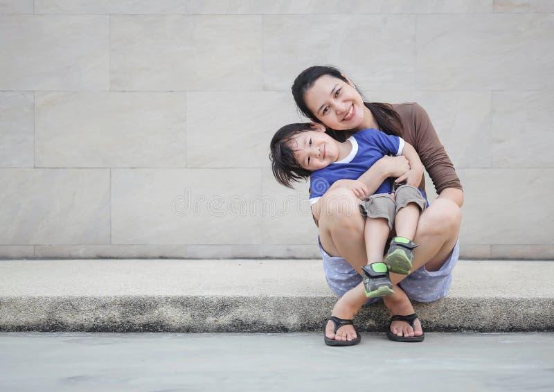 Madre asiatica del primo piano che tiene suo figlio nel moto di divertimento sul fondo strutturato della parete di marmo con lo s fotografia stock libera da diritti