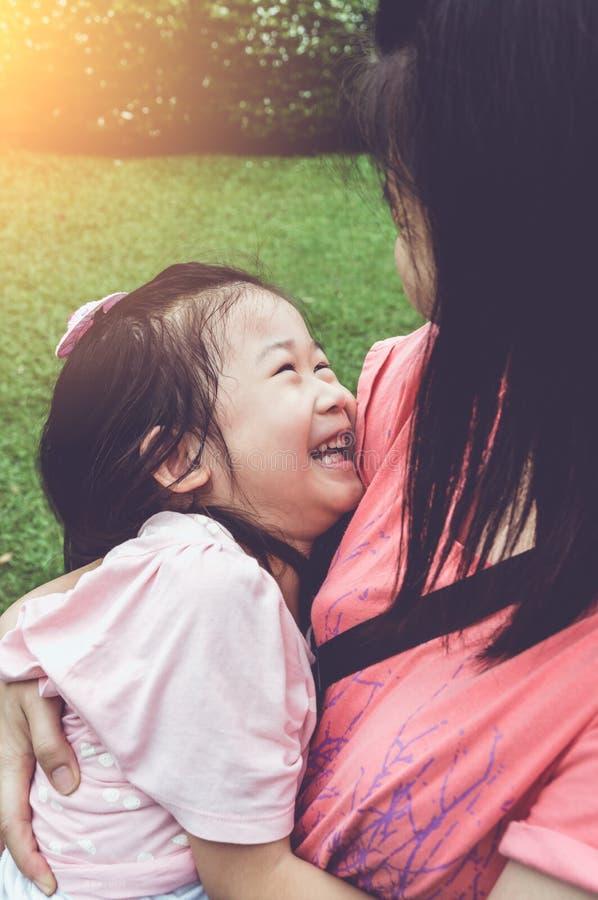 Madre asiatica e figlia adorabile che godono insieme e che sorridono fotografia stock libera da diritti