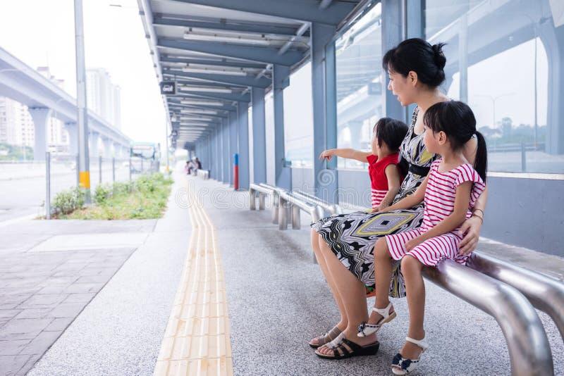 Madre asiatica e figlie cinesi che aspettano un bus fotografia stock