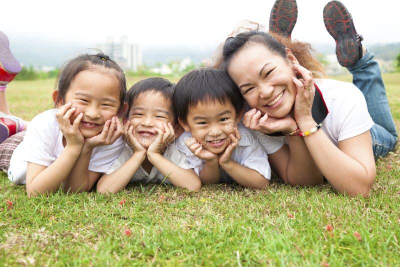 Madre asiatica ed i suoi bambini sul campo verde fotografia stock