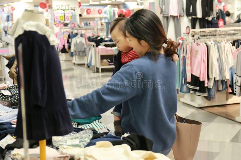 Madre asiatica ed il suo acquisto del bambino nel negozio di vestiti fotografia stock