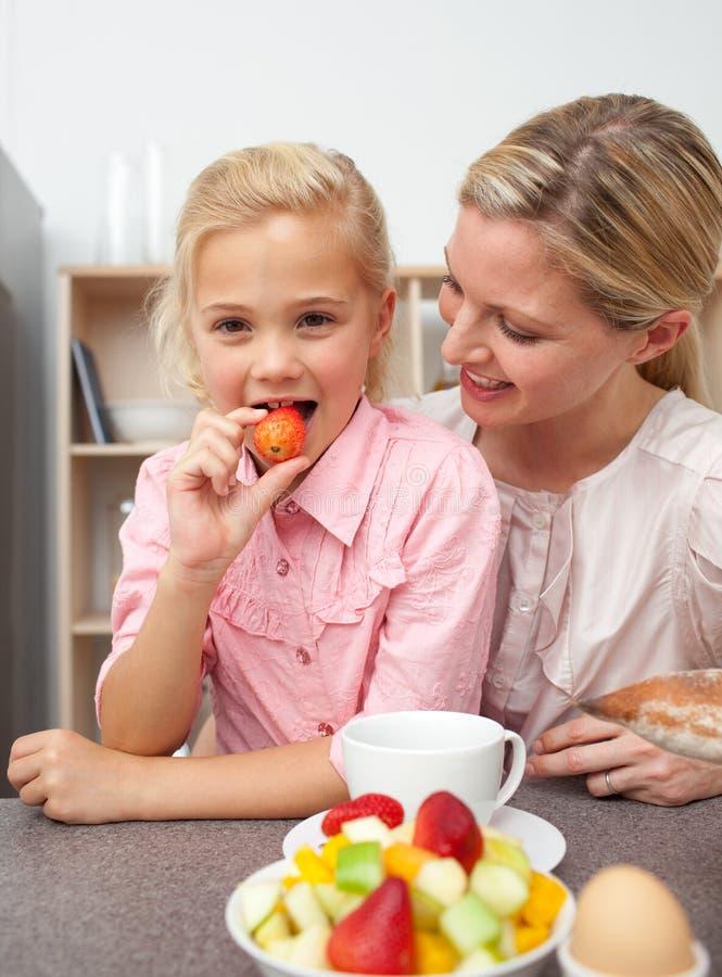 Madre atractiva que come la fruta con su hija foto de archivo libre de regalías