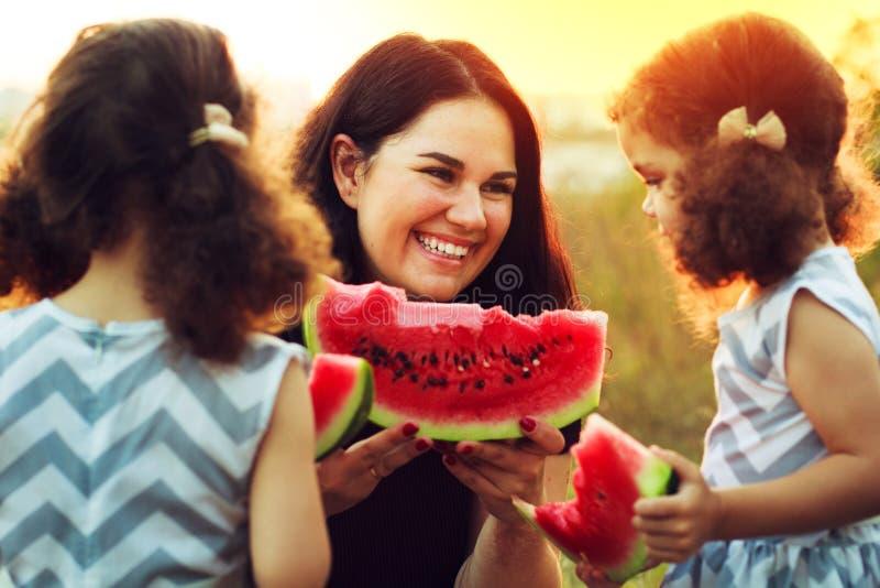 Madre atractiva y pequeñas hijas gemelas lindas con el pelo rizado que gozan de la sandía dulce durante tiempo de la comida campe fotografía de archivo