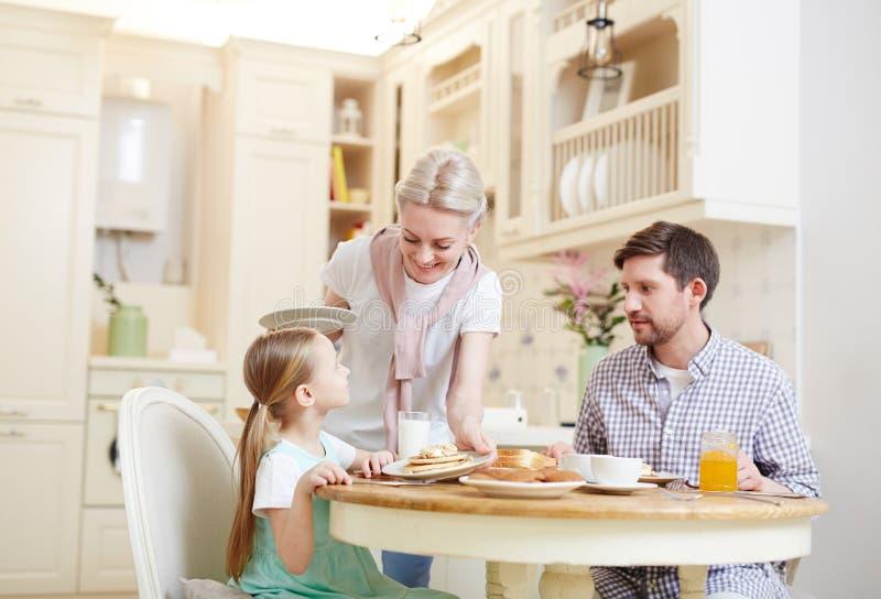 Madre attenta che mette piatto con i pancake immagine stock