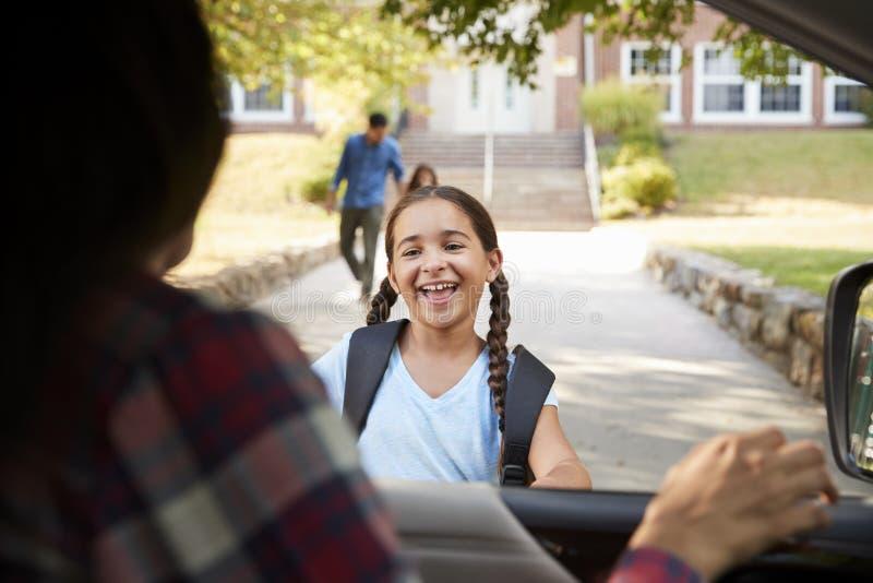 Madre in automobile che raccoglie figlia in Front Of School Gates fotografia stock libera da diritti
