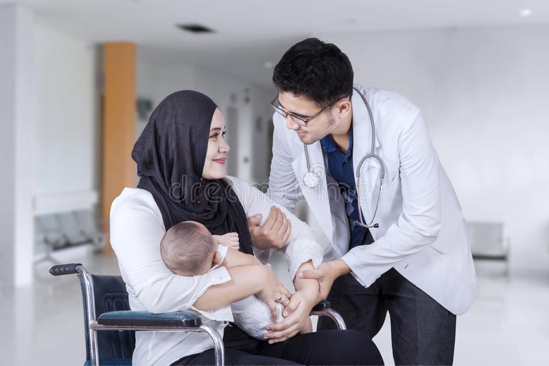 Madre ayudada por el doctor en pasillo del hospital imagenes de archivo