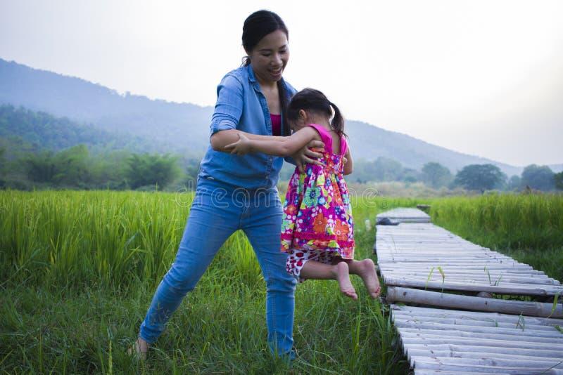 Madre ayudar a su niño a cruzar la corriente, hija de elevación de la madre en campo del arroz imagen de archivo libre de regalías