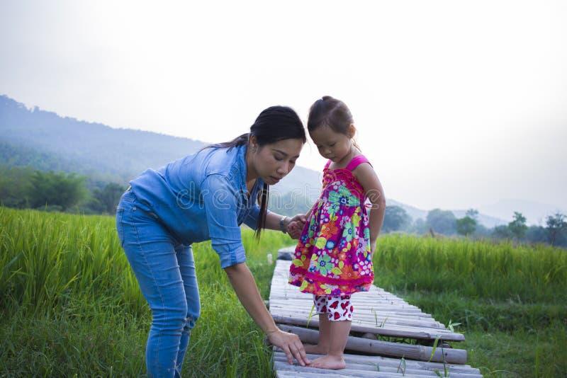 Madre ayudar a su ni?o a cruzar la corriente, hija de elevaci?n de la madre en campo del arroz fotografía de archivo libre de regalías