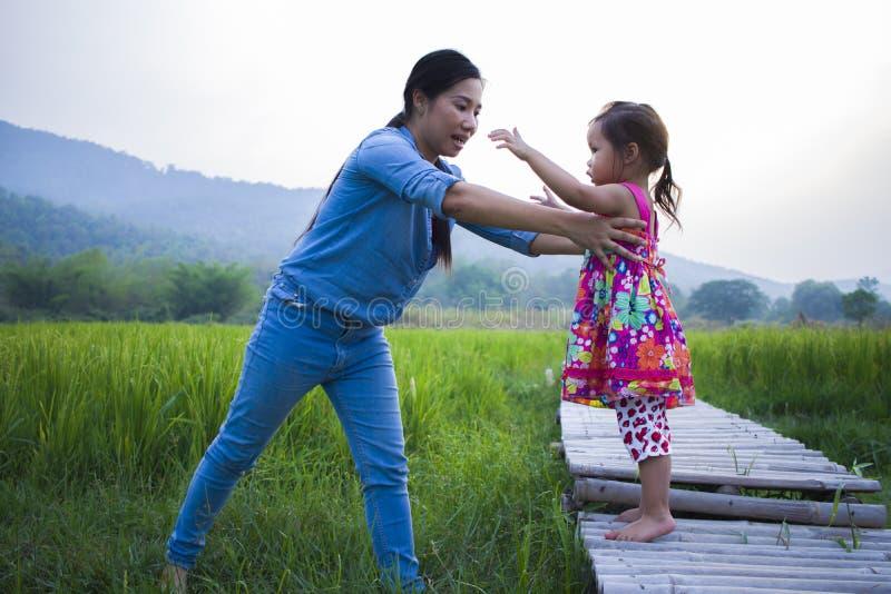 Madre ayudar a su ni?o a cruzar la corriente, hija de elevaci?n de la madre en campo del arroz imagen de archivo libre de regalías