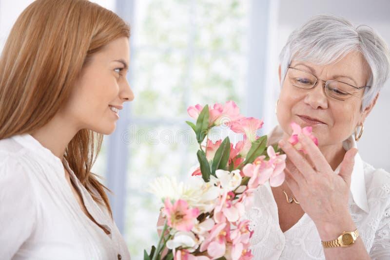 Madre bonita del saludo de la mujer con la sonrisa de las flores imagen de archivo