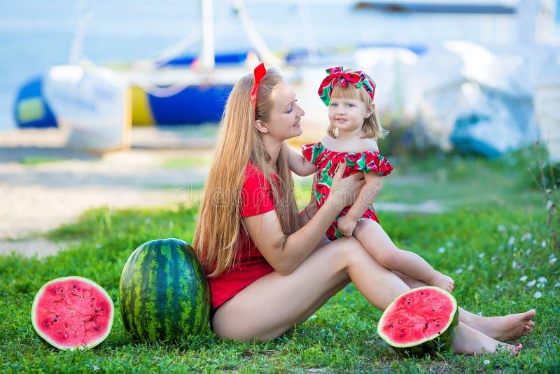 Madre bonita joven que juega con su pequeña hija linda en la playa Mamá de amor que se divierte con su niño en la orilla de mar c imagen de archivo libre de regalías