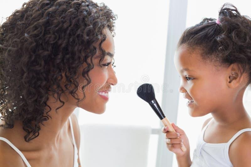 Madre bonita que enseña a su hija sobre maquillaje foto de archivo libre de regalías