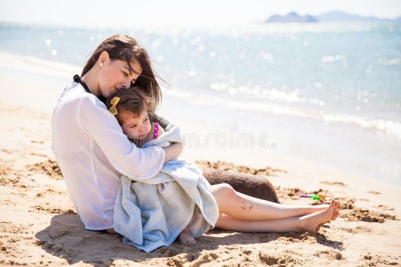 Madre cariñosa en la playa imagenes de archivo