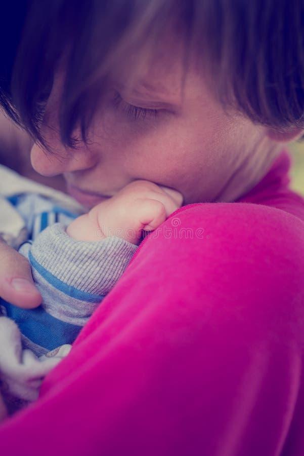 Madre cariñosa que abraza a un bebé recién nacido foto de archivo