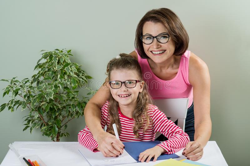 Madre cariñosa que ayuda a su decreto judicial del alumno de la escuela primaria de la hija fotos de archivo libres de regalías