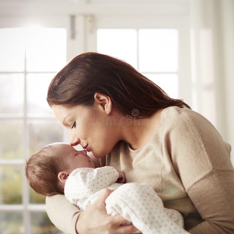 Madre cariñosa que besa y que abraza al bebé recién nacido en casa imagen de archivo libre de regalías