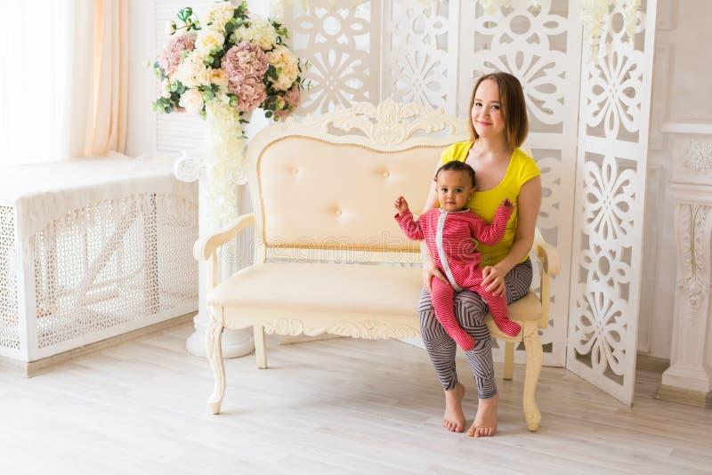 Madre cariñosa que celebra al bebé de la raza mixta en casa fotos de archivo