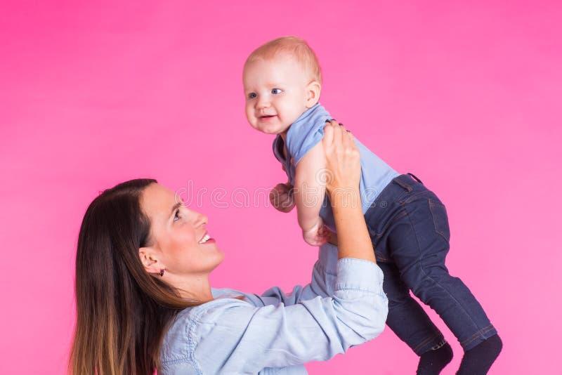Madre cariñosa que juega con su bebé en fondo rosado imágenes de archivo libres de regalías