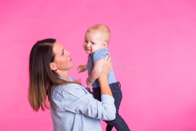 Madre cariñosa que juega con su bebé en fondo rosado imagen de archivo
