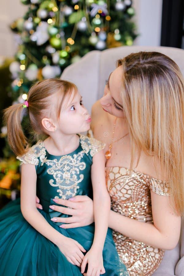 Madre caucásica feliz que se sienta con el vestido que lleva de la pequeña hija cerca del árbol de navidad fotos de archivo