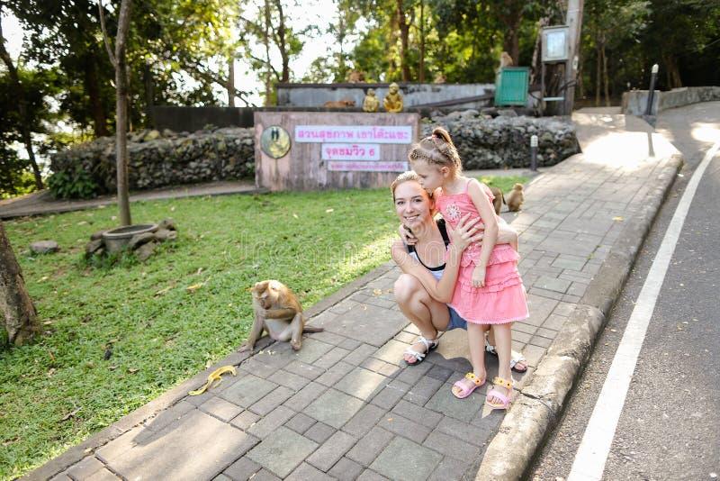 Madre caucásica joven con la hija que coloca monos cercanos en el parque zoológico en Tailandia imágenes de archivo libres de regalías
