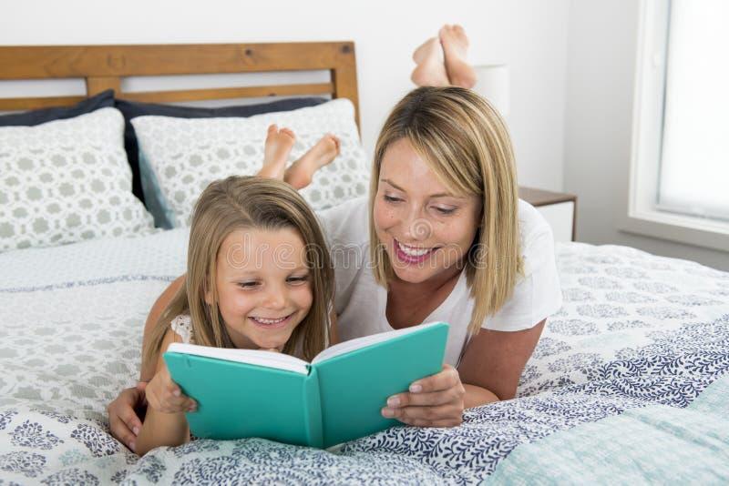 Madre caucásica rubia joven que miente en cama con su dulce joven 7 años de la hija de lectura del dormitorio del libro junto en  fotografía de archivo