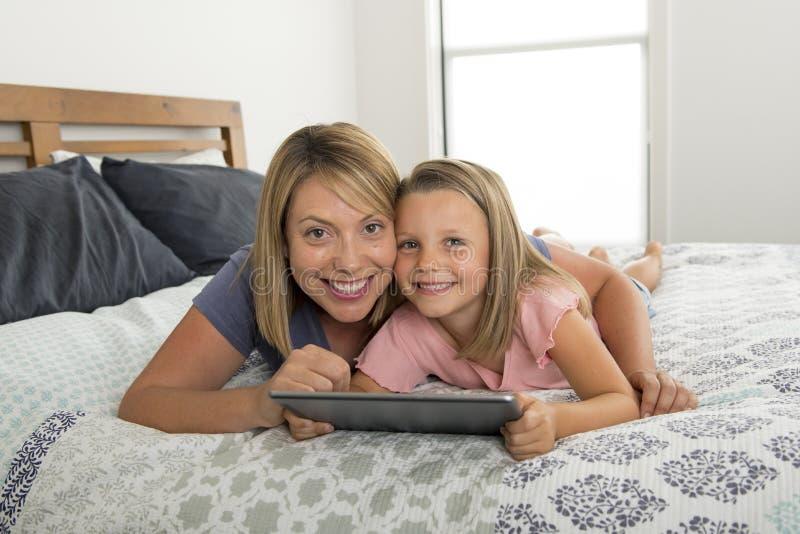 Madre caucásica rubia joven que miente en cama con su dulce joven 7 años de la hija que usa Internet en el cojín digital de la ta fotografía de archivo libre de regalías