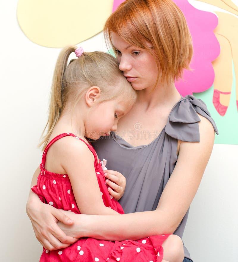 Madre che abbraccia bambino triste fotografia stock
