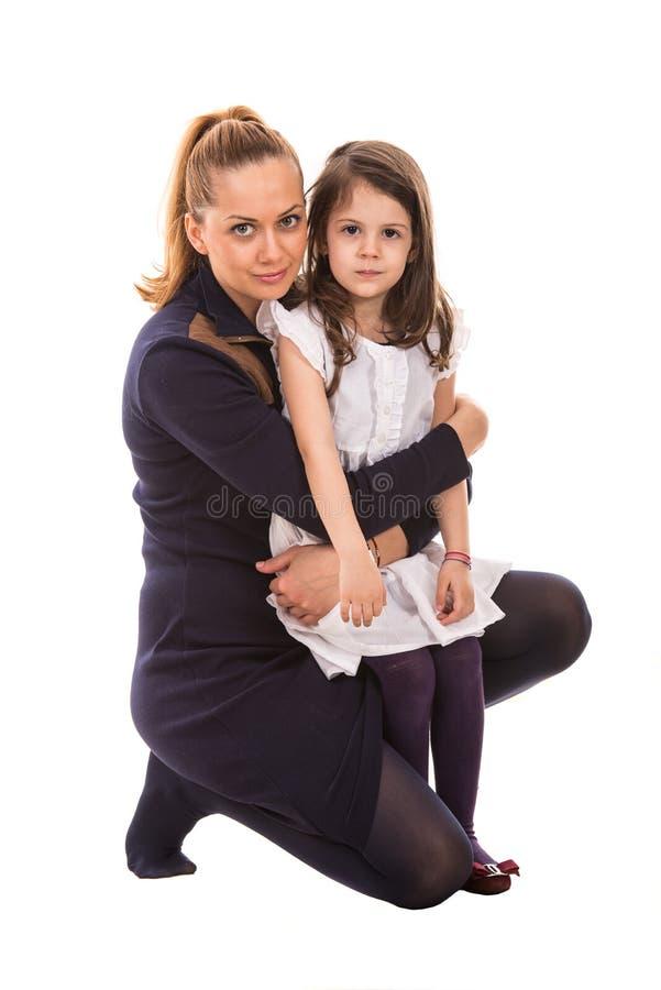 Madre che abbraccia la sua figlia fotografie stock