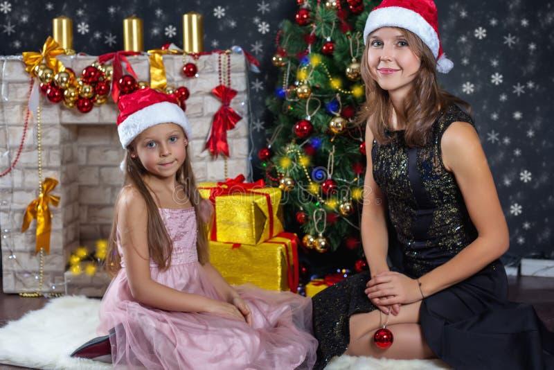 Madre che abbraccia la sua piccola figlia Scene di Natale immagini stock