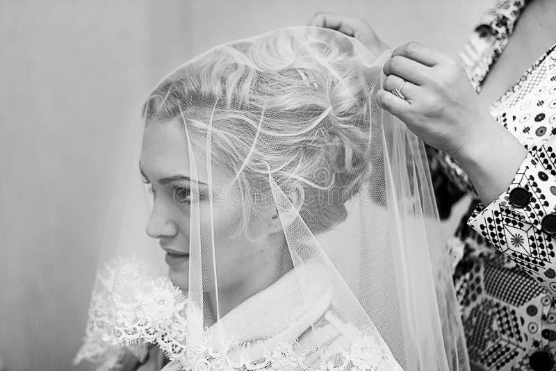 Madre che aiuta giovane bella sposa a vestiresi immagine stock