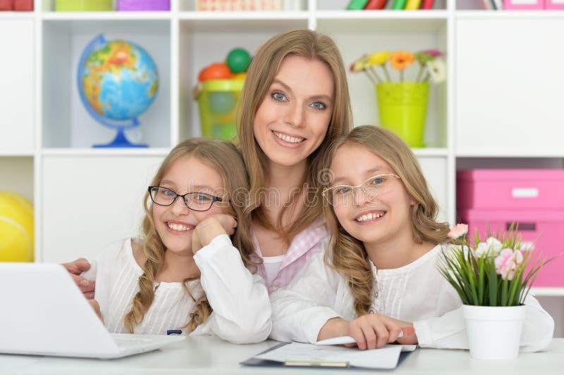 Madre che aiuta le sue figlie con compito fotografia stock libera da diritti