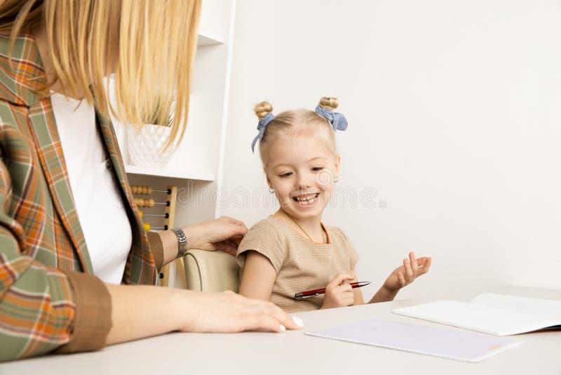 Madre che aiuta poca figlia con compito Concetto di istruzione a domicilio fotografia stock libera da diritti