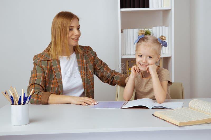 Madre che aiuta poca figlia con compito Concetto di istruzione a domicilio fotografie stock