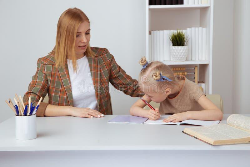 Madre che aiuta poca figlia con compito Concetto di istruzione a domicilio immagini stock