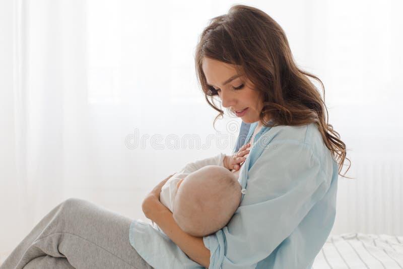 Madre che allatta e che abbraccia il suo neonato fotografia stock libera da diritti
