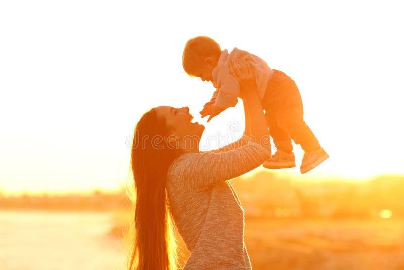 Madre che alza suo figlio del bambino al tramonto immagine stock