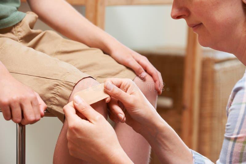 Madre che applica fasciatura adesiva al ginocchio del figlio fotografia stock