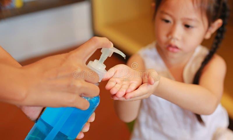 Madre che applica gel di pulizia sulla mano del bambino immagine stock libera da diritti