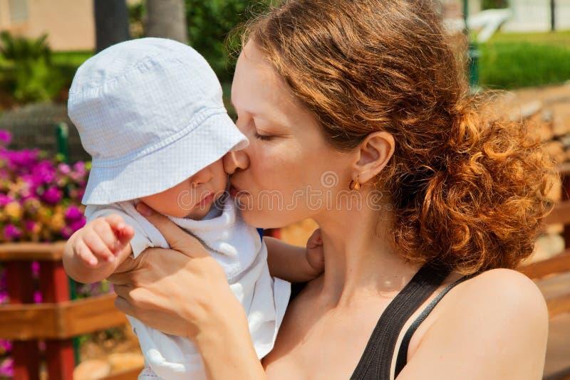 Madre che bacia bambino immagine stock