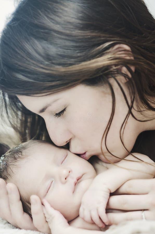 Madre che bacia bambino appena nato immagine stock