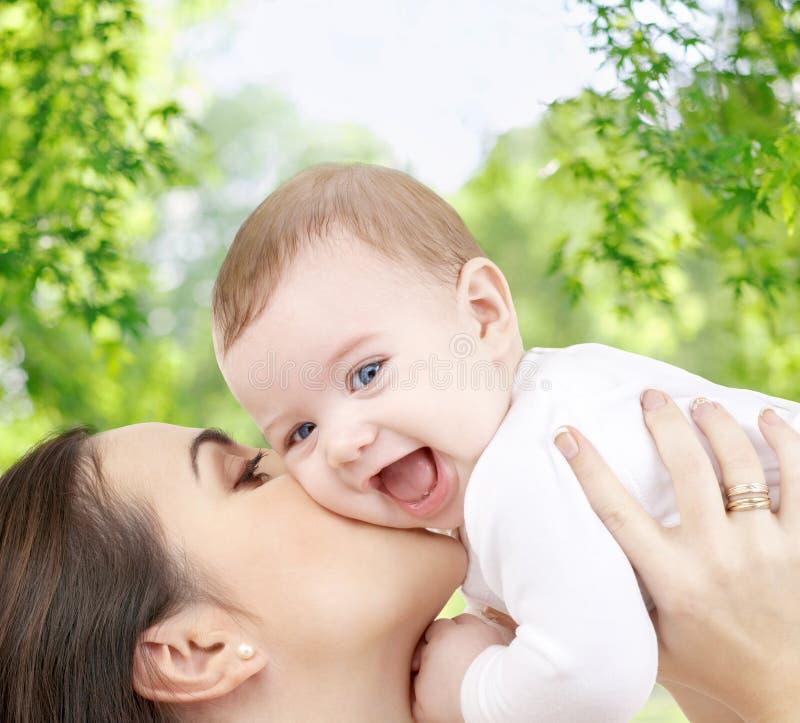 Madre che bacia bambino sopra sfondo naturale verde fotografia stock